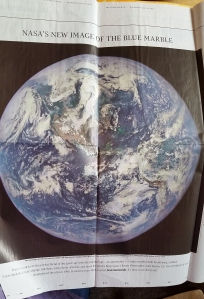 Newspaper clipping of a recent photo of the earth from a satellite launched many years ago.